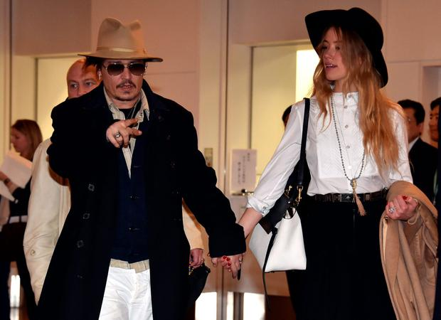 US actor Johnny Depp (L), accompanied by his fiancee US actress and model Amber Heard (R), arrive at Tokyo International Airport on January 26, 2015 for the Japan premiere of his latest movie