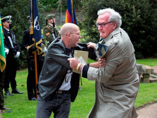 A protester is tackled by the Canadian Ambassador to Ireland, Kevin Vickars at the state event marking the deaths of British Soldiers in The Easter Rising at Grangegorman cemetery today. Photo: Tony Gavin