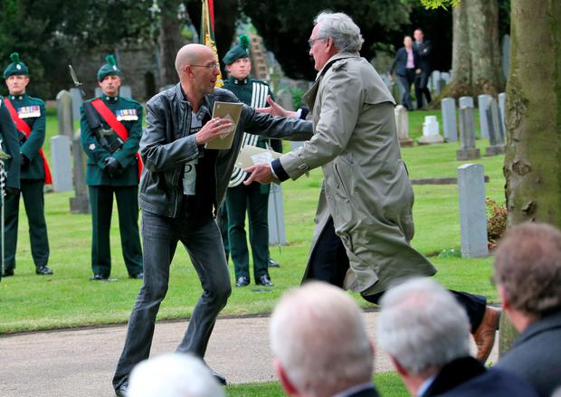 Kevin Vickers Ambassador of Canada to Ireland tackles a protester this morning at Grangegorman Military Cemetery. Picture Colin Keegan, Collins Dublin.