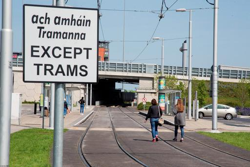 Commuters walking along tram lines at the Red Cow depot on a previous strike day. Photo: Colin O'Riordan