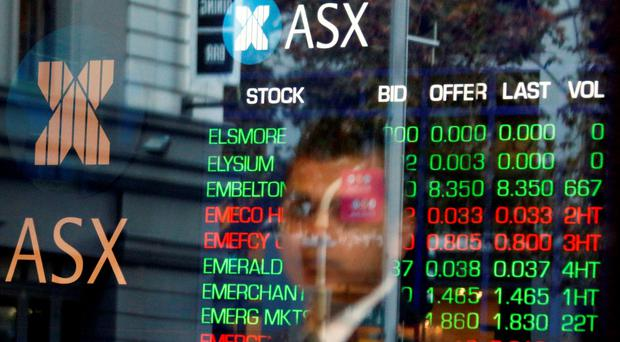 A security guard looks out from a window of the Australian Securities Exchange (ASX) with a board displaying stock prices behind him in Sydney, Australia. Photo: Reuters