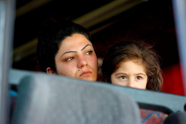 A refugee woman with a child sits in a bus after a police operation to evacuate a makeshift camp at the Greek-Macedonian border near the village of Idomeni, Greece, yesterday. Photo: Reuters/Marko Djurica