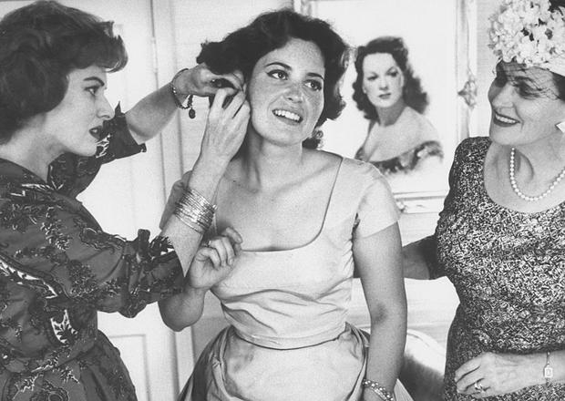 Actress Maureen O'Hara (L) helping daughter Bronwyn Fitzsimons (C) dress for her graduation party. (Photo by J. R. Eyerman/The LIFE Picture Collection/Getty Images)