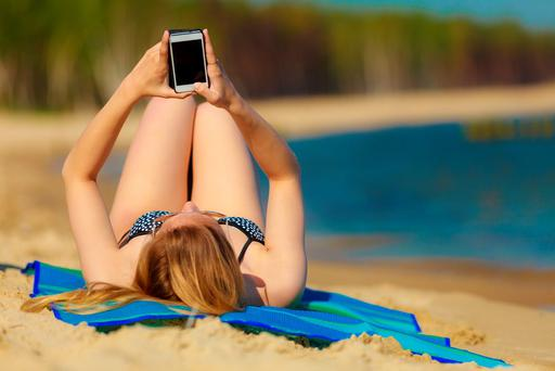 Stock pic. Woman on beach with mobile phone.
