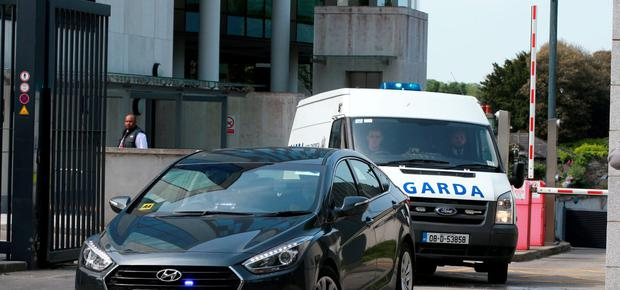 An unmarked Garda car escorts the Garda van with Eamonn Cumberton on board after he was charged with the murder of Michael Barr at the CCJ. Photo: Frank McGrath