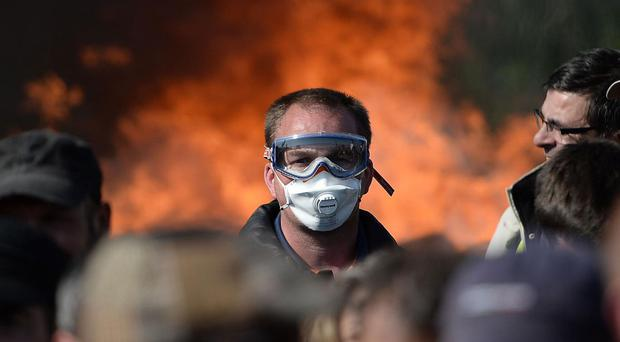 A man with a mask is pictured as workers on strike are evacuated by riot policemen as they block the access to an oil depot near the Total refinery of Donges, western france, on May 27, 2016 to protest against the government's planned labour law reforms AFP/Getty Images