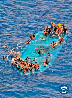 People ask for help after their boat overturned off the Libyan coast Thursday. (EUNAVFORMED via AP)