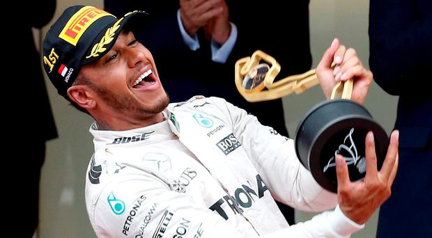 Mercedes F1 driver Lewis Hamilton celebrates on the podium after winning in Monaco. REUTERS/Eric Gaillard