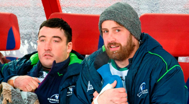 Connacht's Denis Buckley, left, and Aly Muldowney attempt to keep warm on the team bench during their trip to play Enisei-STM in Russia SPORTSFILE. Photo: Denis Prikhodko / Sportsfile