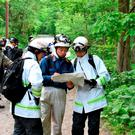 Rescuers serach for a 7-year-old boy who is missing in a Japanese forest in Nanae town (Kyodo News via AP)