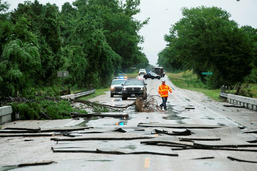 David Goldstein, a construction inspector with Texas Deptartmen of Trasnsportation, looks over the damage to the FM 2104 bridge over Pin Oak Creek near Smithville, Texas (Jay Janner/Austin American-Statesman via AP)