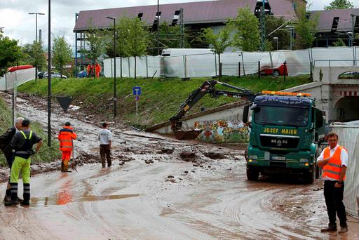 Workers remove mud from a street after the floods in the town of Schwaebisch Gmuend near Stuttgart, Germany, May 30, 2016. REUTERS/Michaela Rehle