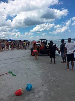 Beachgoers gather after a shark bit a 13-year-old boy at Neptune Beach, Florida.