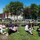 People gather along the canal at Mespil Road in Dublin at lunchtime. Photo: Steve Humphreys