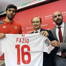 Sevilla's Argentinian defender Federico Fazio (L) poses with with his shirt beside Sevilla's President Jose Castro (C) and sporting director Monchi (R), during his official presentation at the Ramon Sanchez Pizjuan stadium in Sevilla on February 2, 2016. AFP PHOTO / CRISTINA QUICLER / AFP / CRISTINA QUICLER (Photo credit should read CRISTINA QUICLER/AFP/Getty Images)