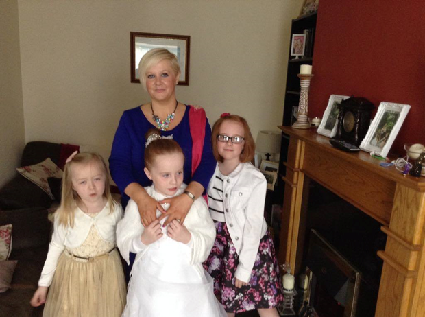 Lucy (middle) with mum Genevieve and sisters Credit: Family photo