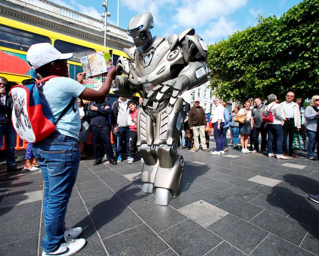 Cillian Chisenga (9) shows a street map to 8ft robot 'Titan' on Dublin's O'Connell Street Photo: Photocall