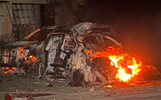 Vehicles burn at the scene a bomb attack on an hotel in Mogadishu, Somalia Wednesday, June 1, 2016. (AP Photo/Farah Abdi Warsameh)