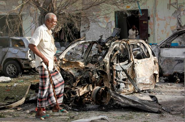 A Somali man walks past a destroyed vehicle at the scene after a bomb attack on Ambassador Hotel in Mogadishu, Somalia, Thursday, June 2, 2016. (AP Photo/Farah Abdi Warsameh)