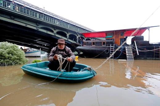 A man sits in a dinghy as he makes his way towards a houseboat along the banks of the Seine River in Paris, France, after days of almost non-stop rain caused flooding in the country