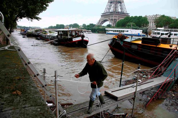 A man uses a footbridge as he leaves his houseboat moored near the Eiffel tower during flooding on the banks of the Seine River in Paris