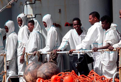 Migrants attend to disembark from the Italian Navy Vega vessel, in Reggio Calabria, southern Italy, after being rescued in the Mediterranean Sea off the coasts of Libya (AP Photo/Adriana Sapone)