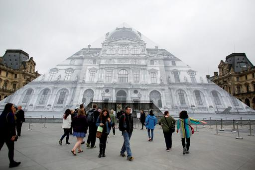 Visitors gather in front of the entrance of the Musee de Louvre which is closed and tourists being turned away, due to the unusually high water level of the nearby river Seine in Paris.(AP Photo/Markus Schreiber)