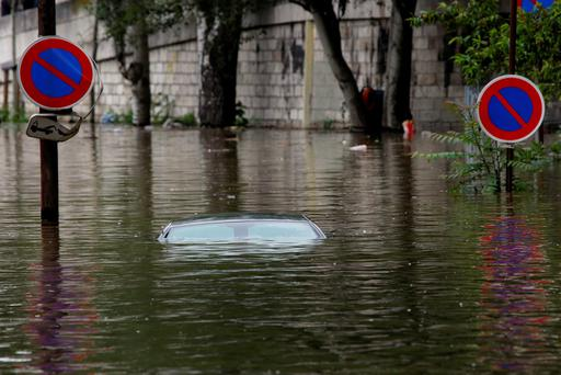 The roof of a car parked in a marked no parking zone sticks out of the water on the flooded banks of the Seine river near the Eiffel tower in Paris. Photo: Jerome Delay)