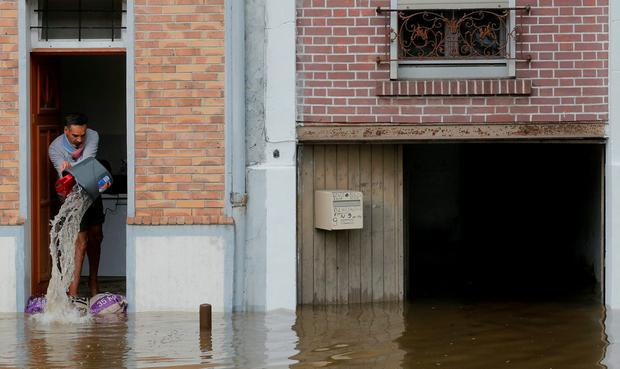 A man scoops water from his house in the flooded suburb of Villeneuve-Trillage in Villeneuve Saint-Georges, outside Paris. Photo: REUTERS/Christian Hartmann