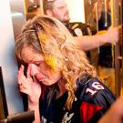 A woman wipes egg off her face after being pursued by anti-Trump protesters while she was leaving the Republican presidential candidate's campaign rally on Thursday. Photo: AP