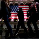 People pass by the New York Stock Exchange (NYSE) in the financial district in the lower Manhattan borough of New York City