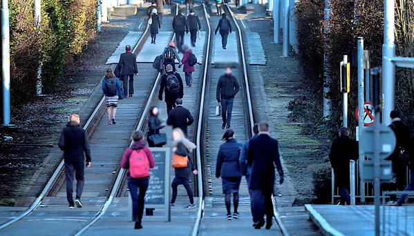 Commuters walking on the tracks during one of the Luas strike days Photo: Steve Humphreys
