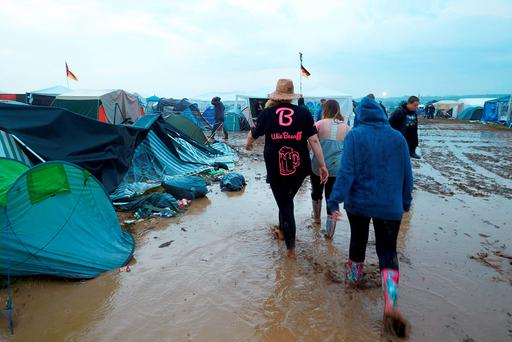 People walk between destroyed tents after a thunderstorm hit the open air music festival ' Rock am Ring' in Mendig, Germany (Thomas Frey/dpa via AP)