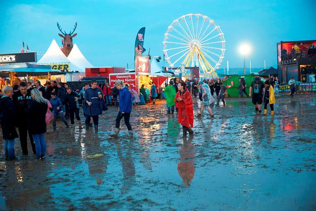 People walk through the mud after a thunderstorm hit the open air music festival ' Rock am Ring' in Mendig, Germany (Thomas Frey/dpa via AP)