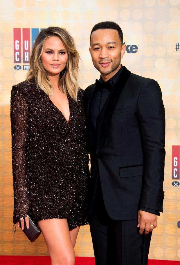 Singer John Legend (R) and wife Chrissy Teigen