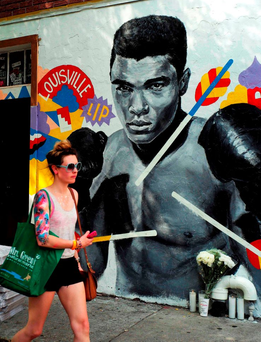 A woman walks past a mural tribute to late boxer Muhammad Ali in New York at the weekend Photo: AFP