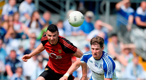 Monaghan's Darren Hughes and Down's Henry Brown in a race for possession in Clones yesterday. Photo: Sportsfile