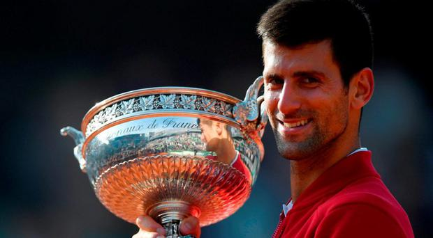Novak Djokovic poses with the trophy after fighting back from being a set down to beat Andy Murray at Roland Garros in the final of the French Open. Photo: Martin Bureau/AFP/Getty Images