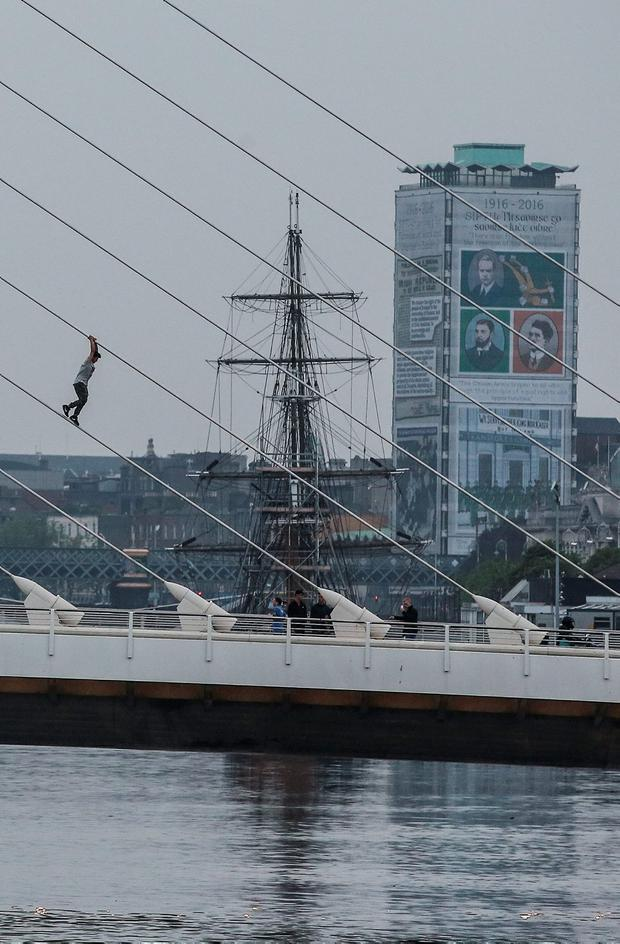 Man climbs to the top of Dublin City's Samuel Beckett Bridge. Photo: Conor McCabe.