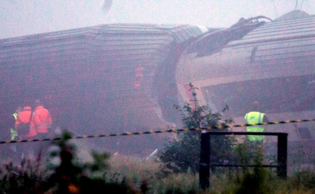 Rescue workers stand near the wreckage of a train crash in Hermalle-sous-Huy, near Liege, Belgium