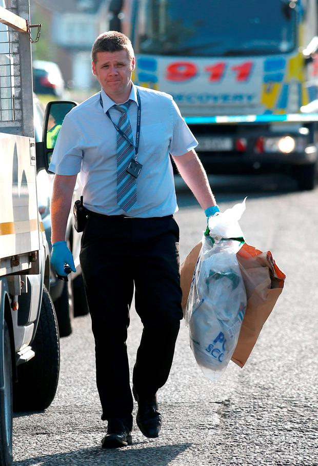 A police officer carries evidence bags at the scene, reportedly in Frankfield Road, in the Stepps area of Glasgow, after a number of people were taken to hospital after an