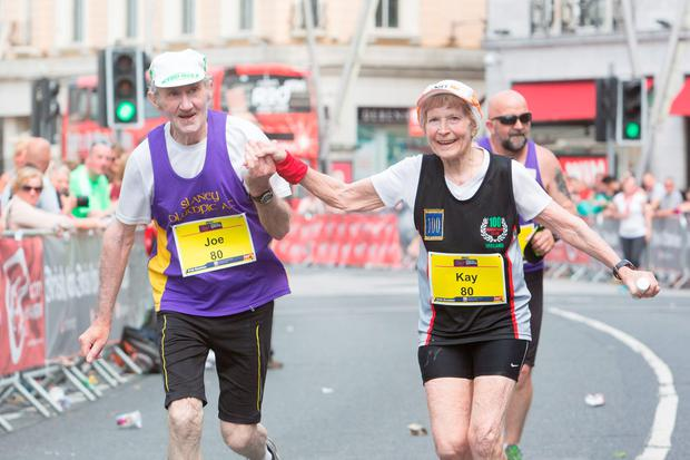 Joe and Kay O'Regan (80) finish the Cork Marathon hand-in-hand, 30 years after their first marathon together. Pic: Darragh Kane