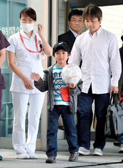Yamato Tanooka, center, who was found after being abandoned by his parents as punishment in a forest, is escorted by his father Takayuki, right, as he leaves a hospital in Hakodate on the northern island of Hokkaido Tuesday, June 7, 2016