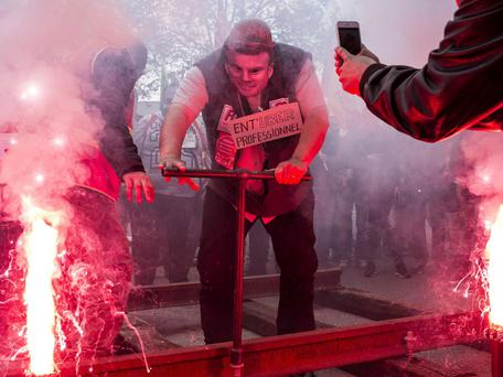 A French rail worker wearing a French Economy Minister Emmanuel Macron mask installs rails during a demonstration in front of the French employers' union MEDEF's branch in Lyon, central France, on Wednesday, June 1, 2016 AP