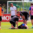Northern Ireland's Kyle Lafferty lies injured during a training session at the Parc de Montchervet, Saint-Georges-de-Reneins. Jonathan Brady/PA Wire.