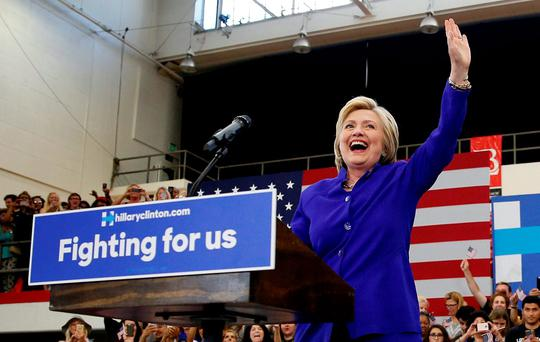 Democratic presidential candidate Hillary Clinton, left, reacts as she takes the stage at a rally. (AP Photo/John Locher)
