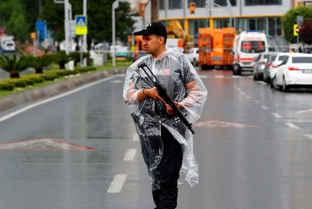 A police officer stands guard near the site where a Turkish police bus was targeted in a bomb attack in a central Istanbul district. Photo: Reuters