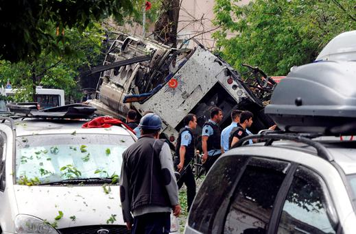Turkish security officials and firefighters work at the explosion site after a bus carrying riot police official was struck by a bomb in Istanbul. Photo: AP
