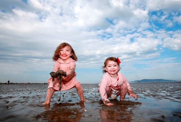 Four year old Lola Murphy pictured with her one year old niece Mila Murphy [both from Dublin] as they play on the wet sand after the tide went out on Dublin's Dollymount strand. Picture: Frank Mc Grath