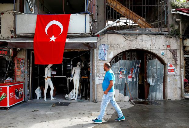 A man walks past by a damaged shop near the scene of Tuesday's car bomb attack on a police bus, in Istanbul, Turkey, June 8, 2016. REUTERS/Osman Orsal